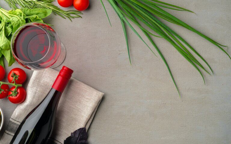 Bottle of red wine on gray surface with vegetables